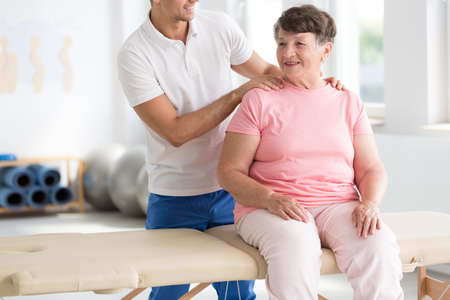 Smiling senior woman relaxing while physiotherapist massaging her
