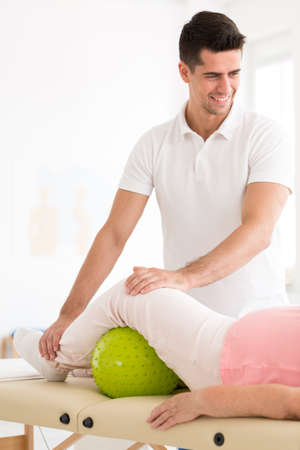 Smiling physiotherapist and elderly patient with green ball under leg