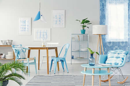 Round table and blue rocking chair in spacious dining room interior with gallery of posters and lamps Reklamní fotografie - 96666472