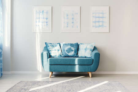 Patterned cushions on turquoise settee against white wall with posters in living room interior with carpet Stock Photo