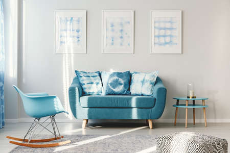 Turquoise sofa with pillows between round table and blue rocking chair in living room interior with posters Standard-Bild - 96666501