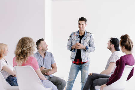 Smiling young man in jeans and denim jacket standing and talking about his progress during group therapy for rebellious youth