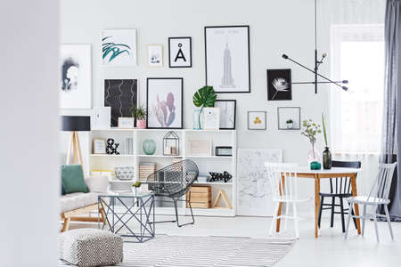 Many modern posters hanging on white wall in stylish living room interior with table