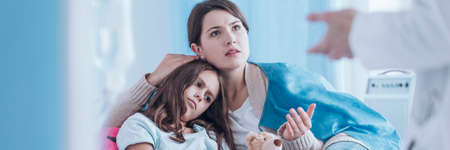 Caring mother talking to a doctor about her daughters health in the hospital Stockfoto
