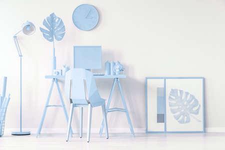 Einfache Plakate auf dem Boden neben dem Schreibtisch in einem blau-weißen Arbeitszimmer Standard-Bild - 96924524