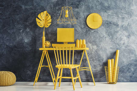 Yellow painted furniture in home office interior with grey textured wall