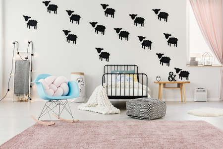 Blue rocking chair on pink carpet in spacious bedroom interior with pouf next to bed against white wall with black sheep stickers
