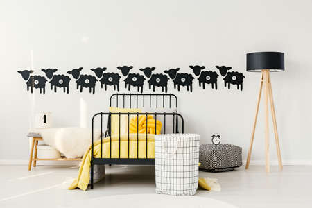 Bag next to yellow bed between bench and wooden lamp in kids bedroom interior with sheep wall stickers