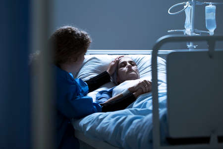 Worried caregiver supporting dying woman with cancer in the hospital Stock Photo