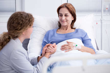 Smiling elderly woman and caring daughter holding her hand in the hospital Stock fotó - 96924618