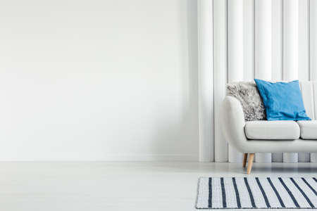 White couch with pillows standing next to an empty wall in a living room interior Banco de Imagens - 104318444