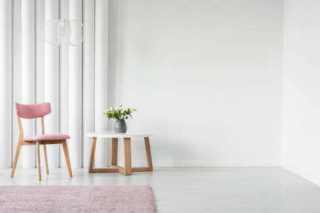 Pink, wooden chair and coffee table next to an empty wall in a living room interior