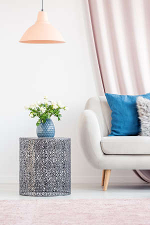 Living room interior with a metal side table, a blue vase and a white couch Stock Photo