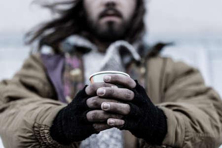 Foto van een dakloze man met close-up van vuile handen met een papieren beker