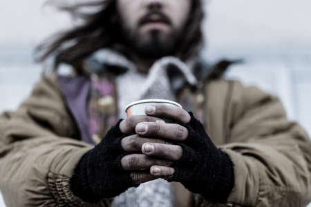 Photo of a homeless man with close-up of dirty hands holding a paper cup Stock Photo