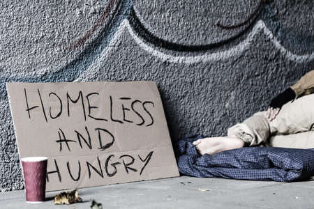 Paper cup standing by the handmade sign of a homeless and hungry man
