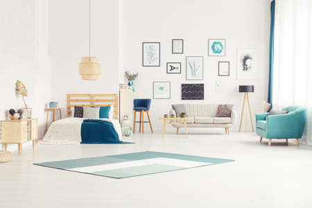 Blue carpet and armchair in bright open space interior with bed near sofa next to wooden lamp 版權商用圖片