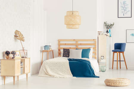 Wooden cupboard and pouf next to bed with blue bedsheets in bedroom interior with lamp Stock fotó - 96924667
