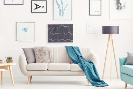 Blue blanket on settee next to lamp in cozy living room interior with gallery of posters