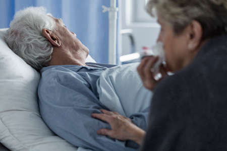 Dead elderly man lying in hospital bed while wife wiping tears