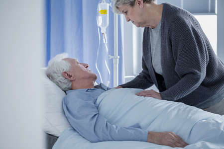 Senior woman taking care of dying husband connected to a drip Stock Photo