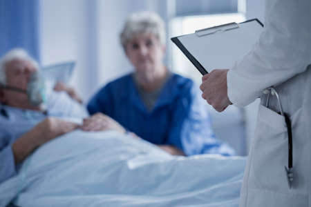 Doctor with stethoscope in the pocket of a white apron holding results of elderly patient Stock fotó - 96924676