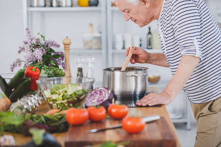 Elderly man smelling healthy tomato soup in the kitchen with vegetables