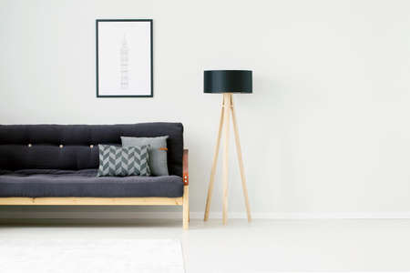 Wooden lamp against white, empty wall in living room interior with gray pillows on black couch