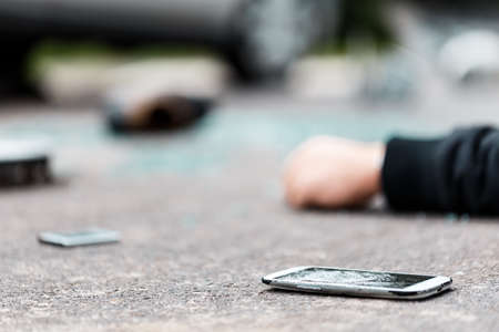 横断歩道の事故の後、路上に横たわっている壊れた電話 写真素材
