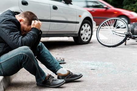 歩道に座って、自動車事故を引き起こした後に泣いている男
