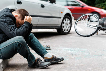 Man sitting on the sidewalk and crying after causing a car accident
