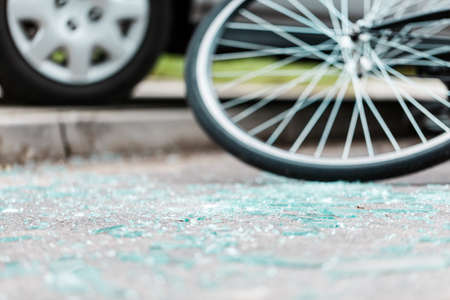 Photo of broken glass on the road with blurred car and bike in the background
