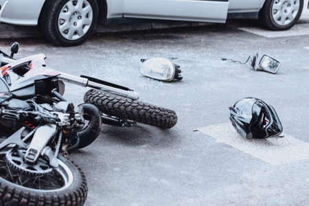 Car mirror, headlight, helmet and motorcycle lying on the road after a car crash Standard-Bild