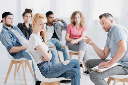 Teenage girl sitting with her arms closed and listening to psychologist during therapy session Stock Photo
