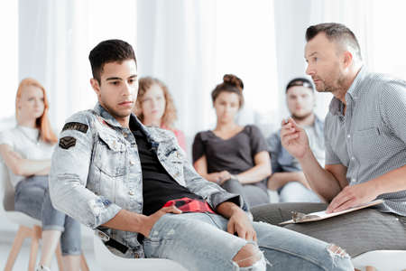 Male therapist talking to rebellious teenager about his problems