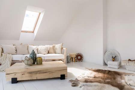 木製のボードとベージュのソファで作られたテーブル付きのリビングルームの床に民族のお土産や毛皮