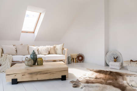 Ethnic souvenirs and fur on floor in living room with table made from wooden board and beige sofa 스톡 콘텐츠