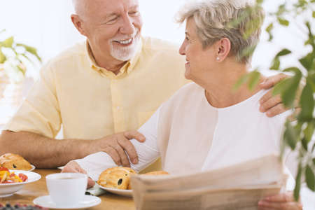 Happy grandfather hugging his wife while eating breakfast at a table