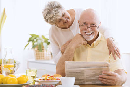 Smiling elderly man reading a newspaper in the morning with his happy wife 写真素材