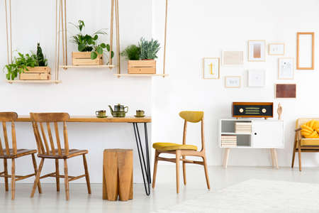 Kettle on dining table in white room interior with wooden chairs and stools near radio on cupboard