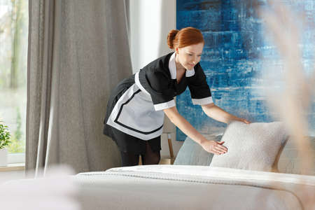 Professional maidservant putting a cushion on a bed in accordance with hotel standards Imagens