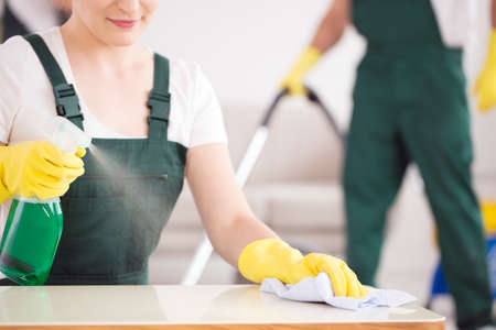 Close-up of cleaning lady spraying the table with green detergent 스톡 콘텐츠
