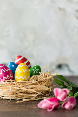 Colorful easter eggs in a nest next to pink tulip Stock Photo