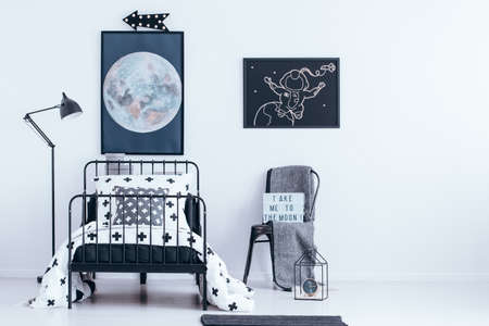 Moon and astronaut posters hanging above black, metal bed in bright bedroom interior for a kid