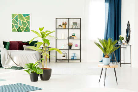 Palm on wooden stool and green painting on white wall above bed in floral bedroom interior