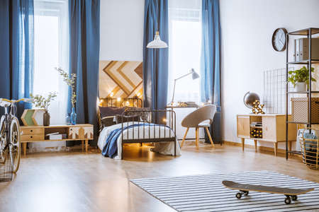 Skateboard on rug in spacious bedroom interior with wooden furniture, blue drapes and lights on the bed
