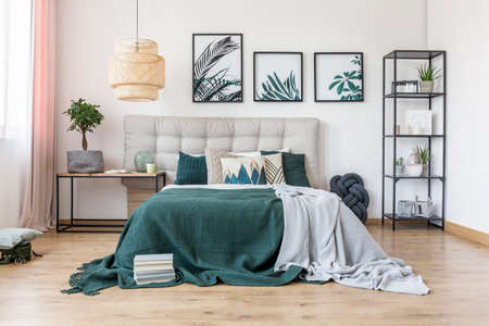 King-size bed with wool blankets and books on the floor in cozy bedroom interior