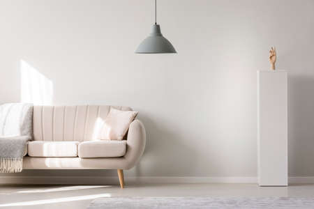 Sofa and grey lamp hanging in living room interior with empty white wall