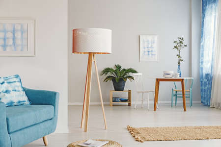 Oversized, wooden lamp standing in open space apartment interior between the living and dining room Stock Photo
