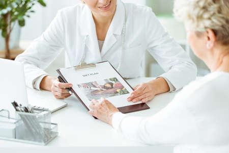 Close-up photo of dietician showing diet plan to her patient